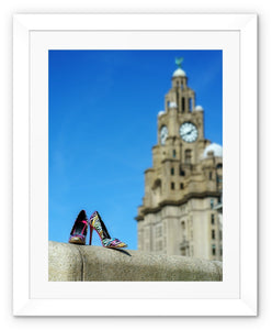 Framed print with white border showing Liverpool liver building with pair of multi-coloured high heeled shoes in foreground
