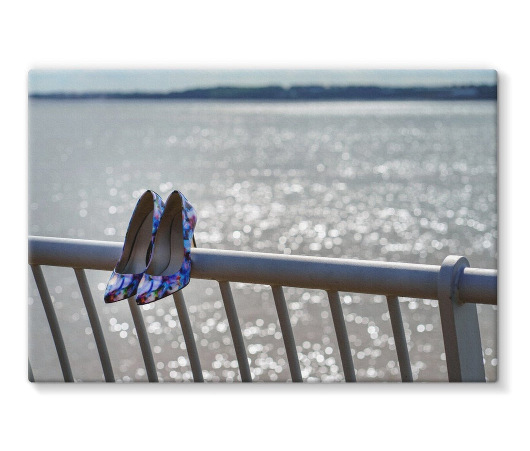 Canvas print of women's shoes on railings next to River Mersey