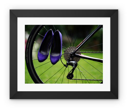 framed print with back border showing pair of purple high heeled ladies  shoes hanging of spokes of the rear wheel of a bicycle