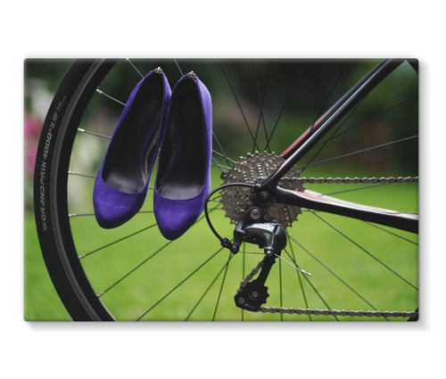 canvas print with back border showing pair of purple high heeled ladies  shoes hanging of spokes of the rear wheel of a bicycle