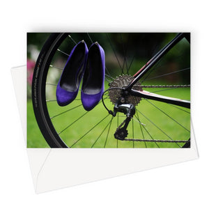 greeting card showing pair of purple high heeled ladies shoes hanging of spokes of the rear wheel of a bicycle