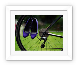 framed print with white border showing pair of purple high heeled ladies  shoes hanging of spokes of the rear wheel of a bicycle
