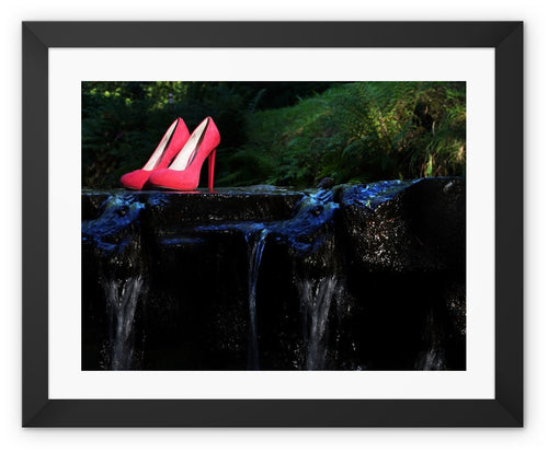 Frame Print with black border showing pair of red ladies high heeled shoes placed on a rock in a river