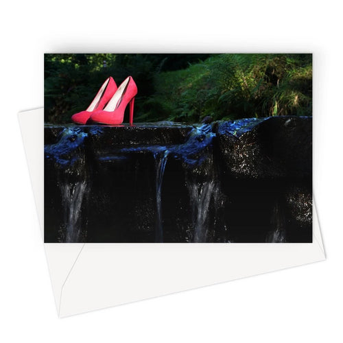 Greeting card showing pair of red ladies high heeled shoes placed on a rock in a river