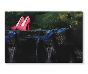 Canvas Print with black border showing pair of red ladies high heeled shoes placed on a rock in a river