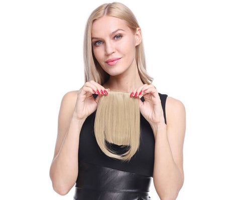Model holding up blonde clip on blunt bangs