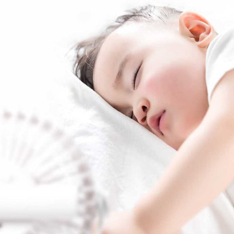 Baby sleeping peacefully with cooling clip on fan quietly blowing cool air at baby
