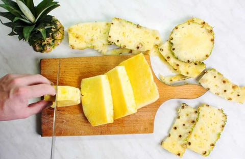 Top view of person cutting pineapple with knife