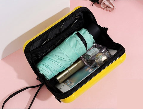 Mini suitcase handbag opened, showing umbrella, fragrance, sunglass, lipstick and smartphone inside