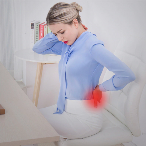 Office worker sitting on a chair whilst holding her back and neck in pain