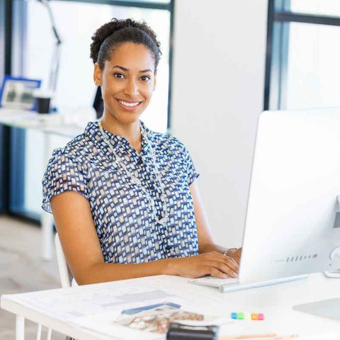 Woman sitting on work desk smilling, happy with the buttock gel seat cushion