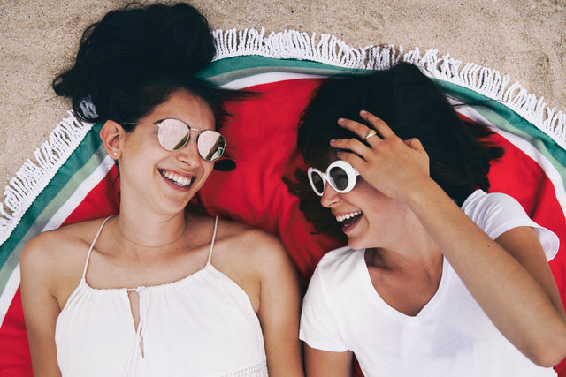 Two woman with sunglasses lying on a colorful green and red round beach towel, laughing happily.