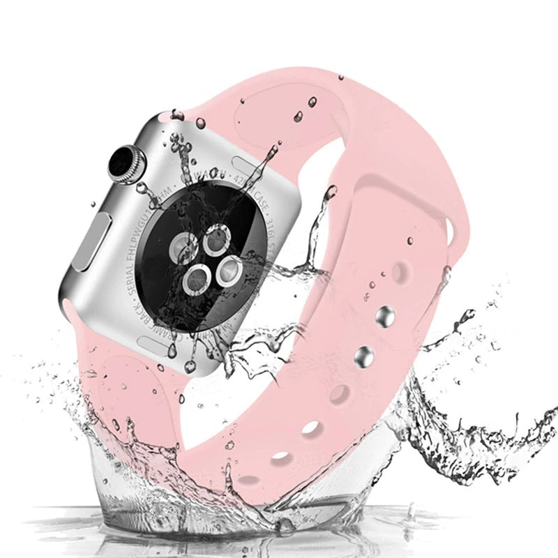 Apple Watch with silicone sport band in pink with water splashing onto it, showing that it is water resistant
