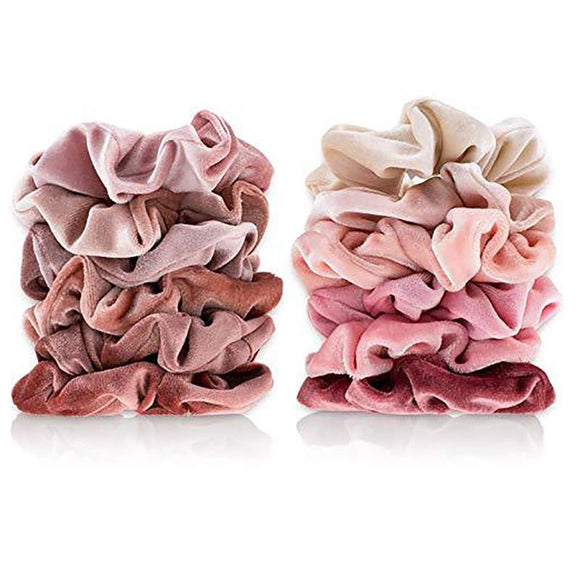 Twelve velvet scrunchies of different nude and rosy hues stacked up