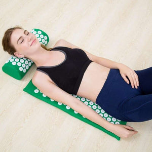 Girl lying on the acupressure mat and pillow, feeling good
