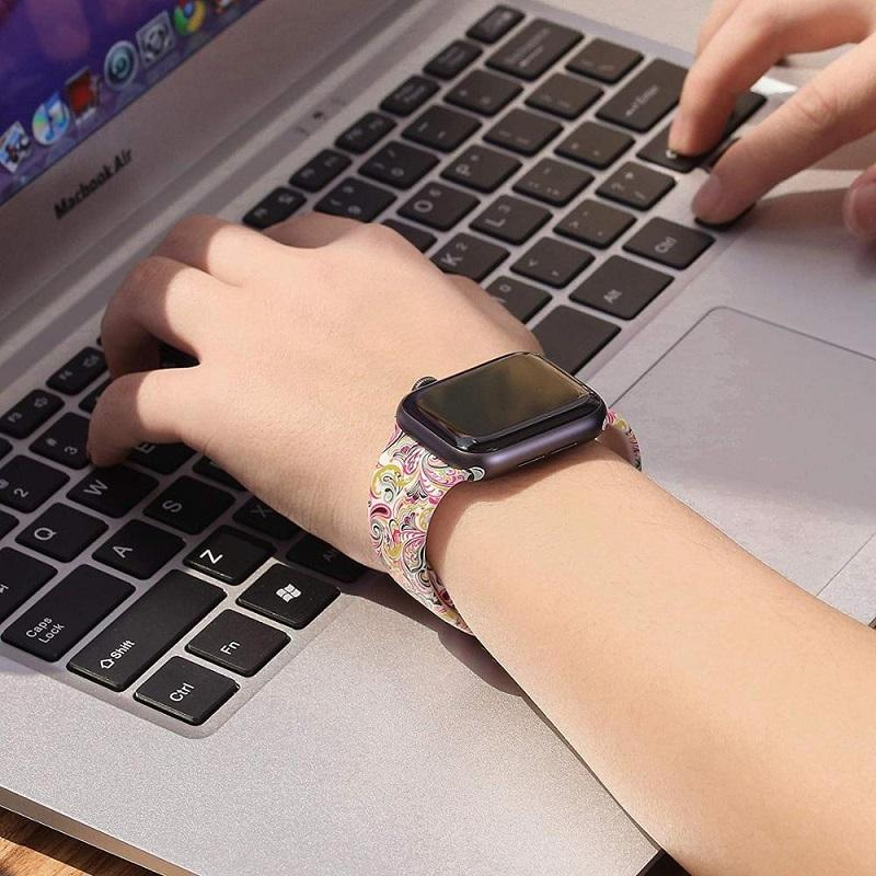 Hands typing on keyboard, wearing an Apple Watch with colorful printed silicone wristband.