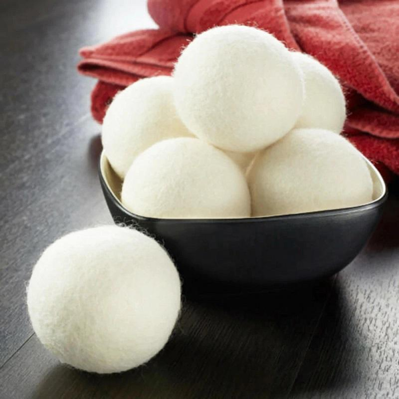 Six white wool dryer balls. five stacked up on a brown cermic bowl and the sixth one sitting on a wooden table surface