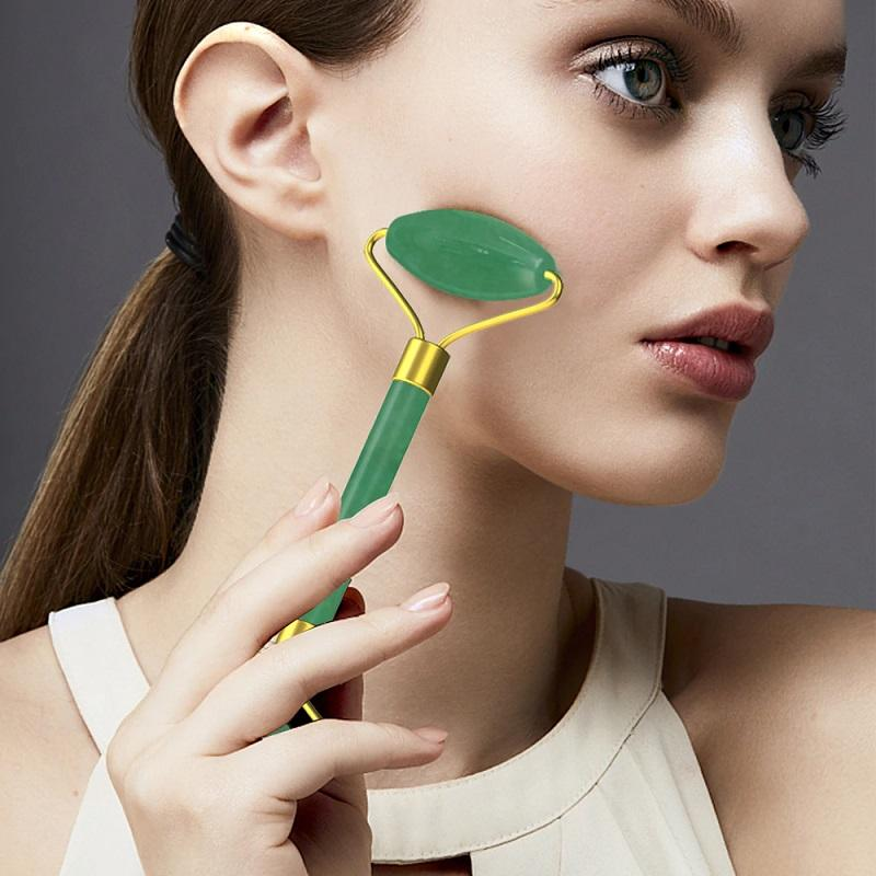 Woman holding the jade roller on her cheek