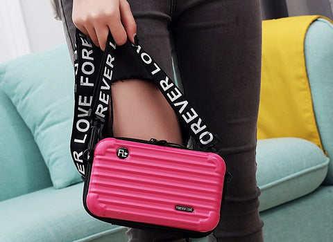 Model wearing pink mini suitcase shaped crossbody