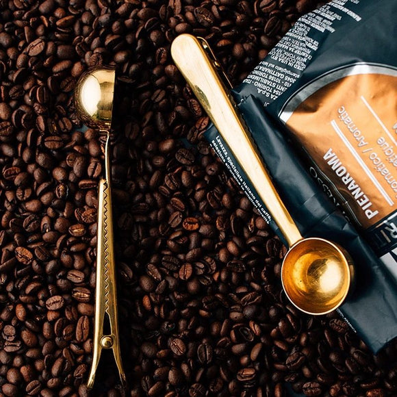 2 pieces of Multifunctional Stainless Steel Spoon cum Bag Clip in gold, lying on a mound of coffee. One clip is clipped to a black coffee bag