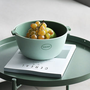 Small double layer colander with grapes displayed on coffee table