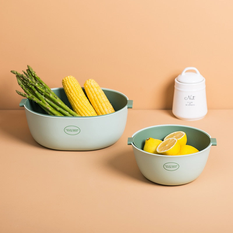 One large double layer colander, one small round double layer colander filled with asparagus, corn and lemons