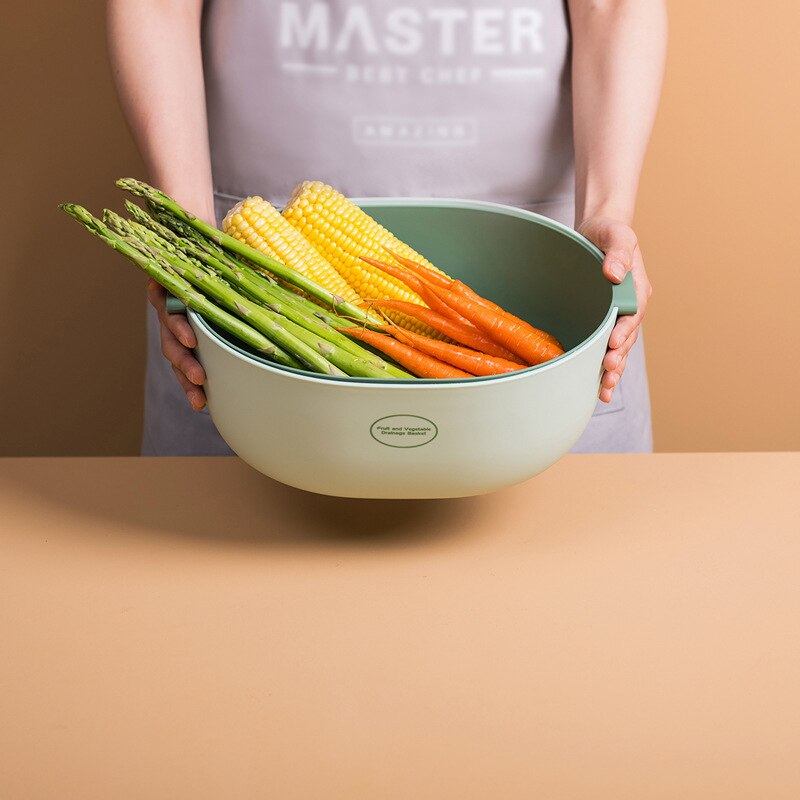 Person holding a large double layer colander filled with asparagus, corn and carrots