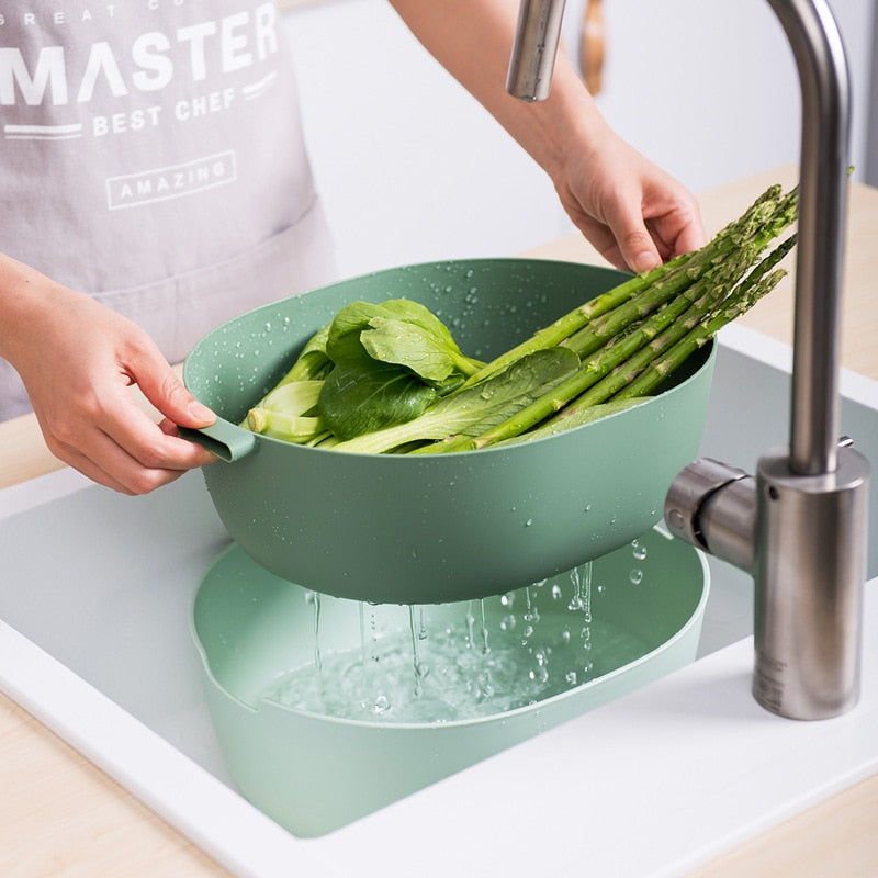 Person washing asparagus in the sink with the double layer large colander, demonstrating how to strain the vegetables
