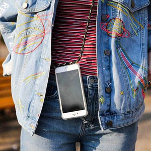 Person with denim jacket wearing iPhone case with striped cord like a crossbody sling