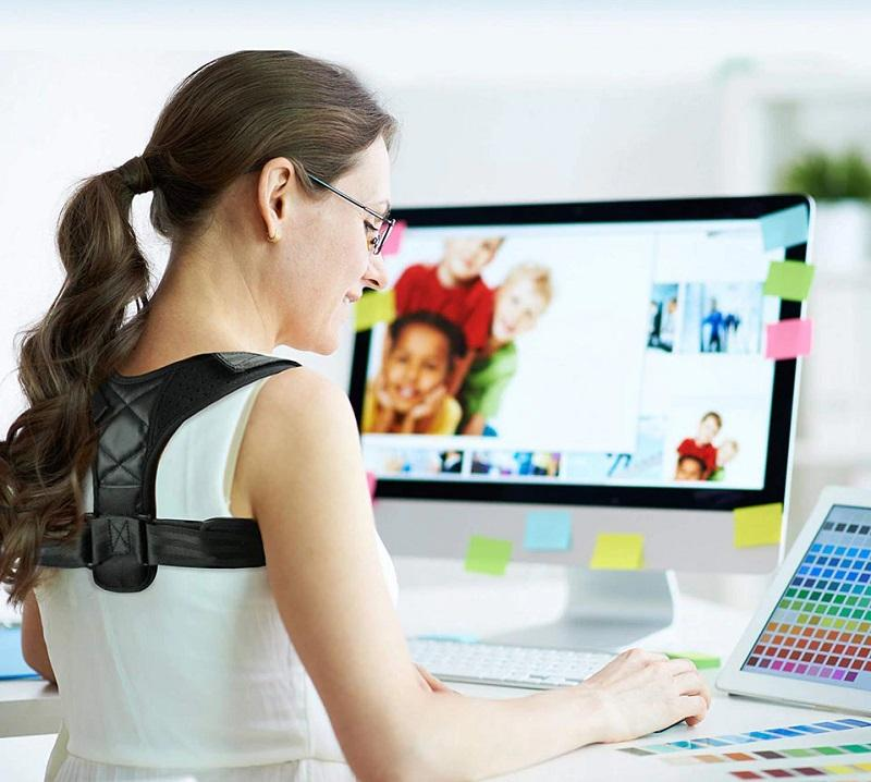 Woman working on desktop, wearing the unisex posture corrector by leBoosh!