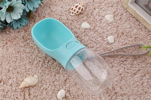 Blue portable dog water bottle lifestyle shot for instagram, on beige textured carpet with sea shells surrounding it