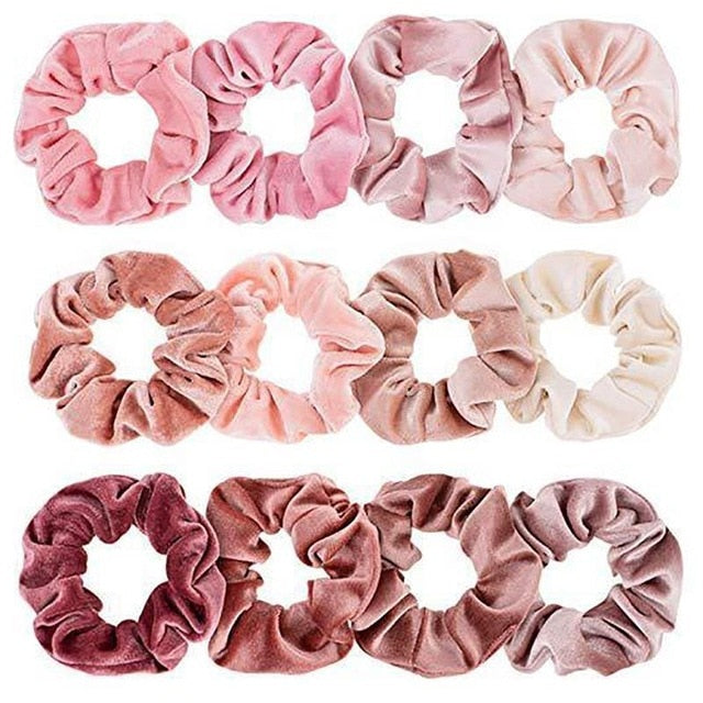 Twelve velvet scrunchies of different nude and rosy hues in flat lay