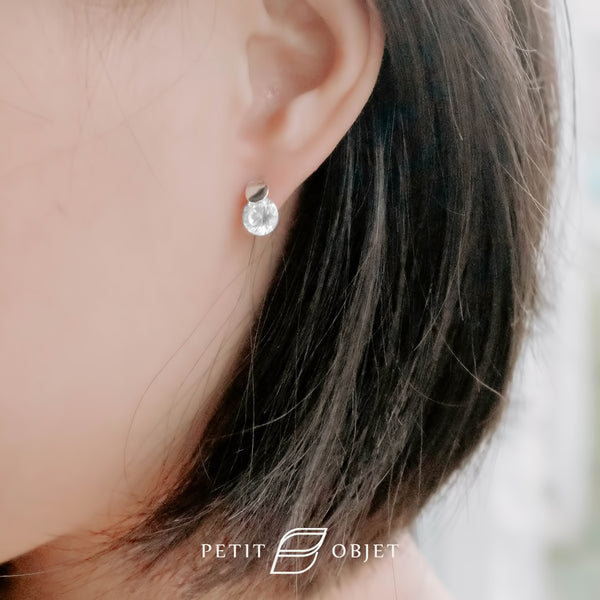 A circular diamond earring with white gold organic shape plate.