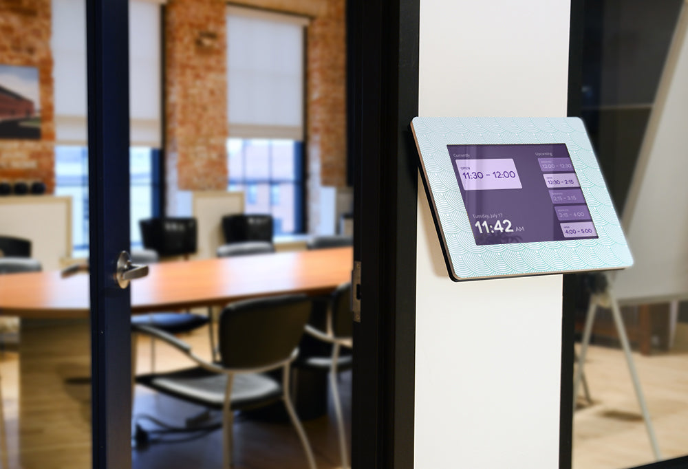 An Angled Wall Mount kiosk mounted outside of a conference room, displaying a room schedule.