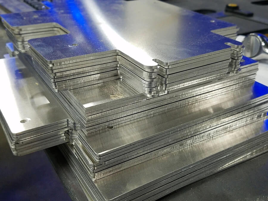 A stack of metal plates used for kiosk brackets.