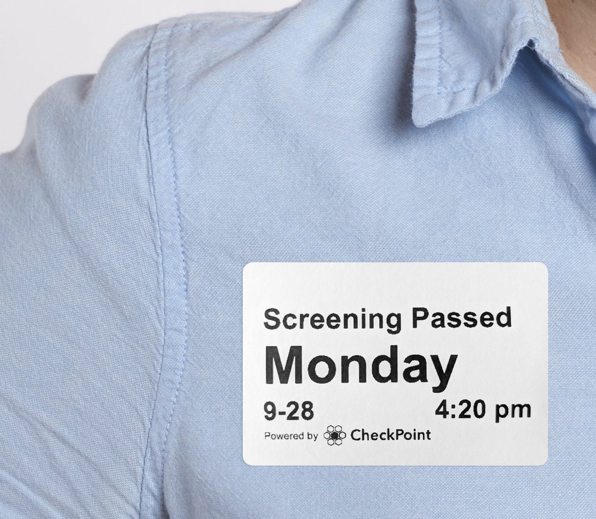 A person's shirt with a printed badge. The badge includes the date and time in large, clear text.