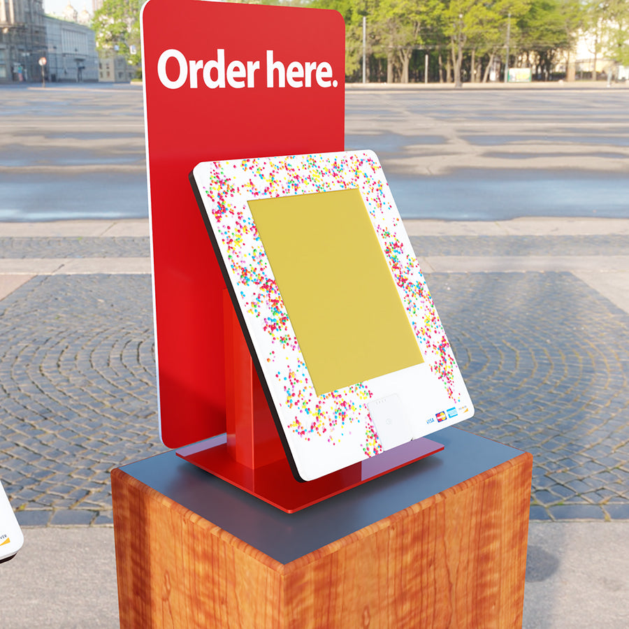 A countertop kiosk with a card reader and custom backdrop.