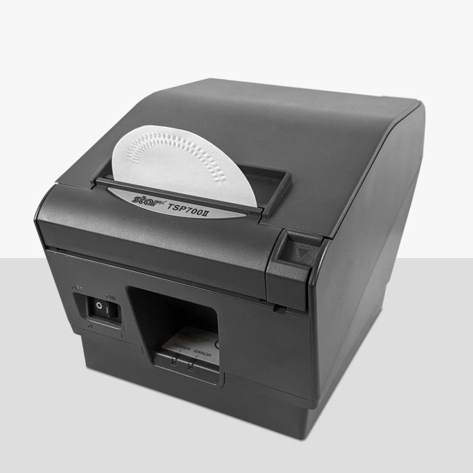 A fabric cleaning card sticking out of the print head of a Star thermal printer.