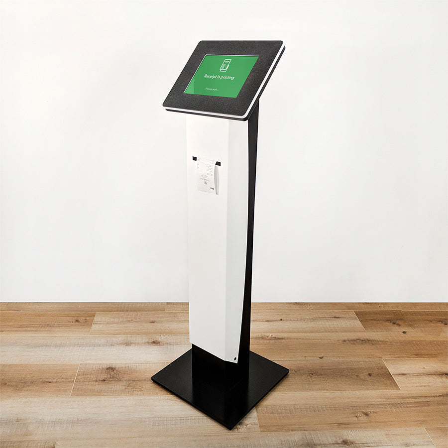A standing kiosk with a printer slot for receipts. The iPad screen displays a 'Printing...' status message.