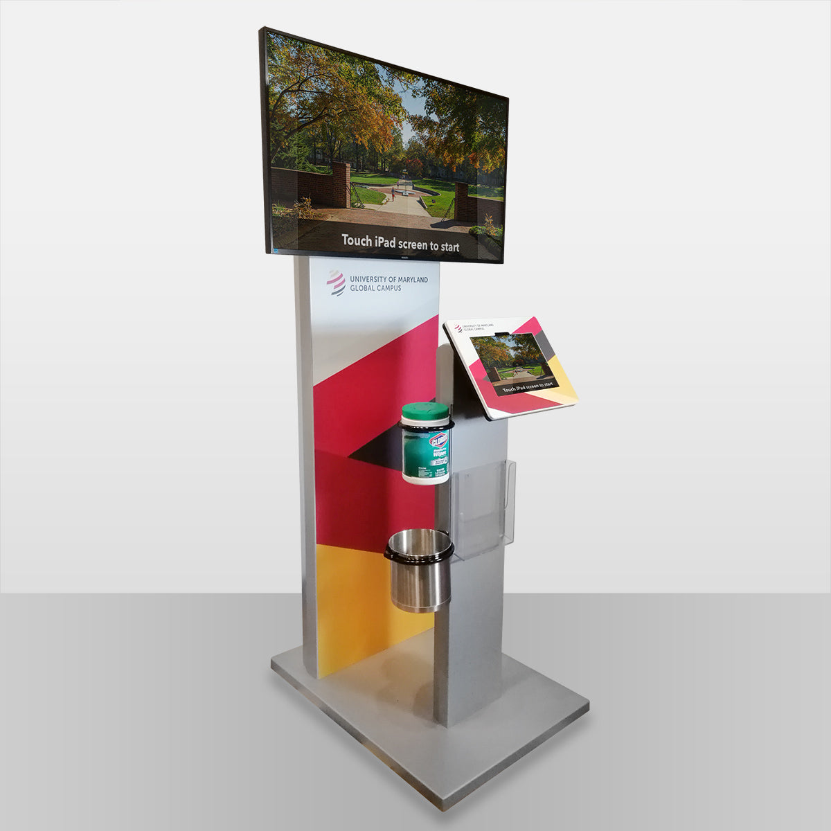 A freestanding tablet kiosk with an external monitor attachment. The tablet screen is mirrored to the external screen for high visibility.