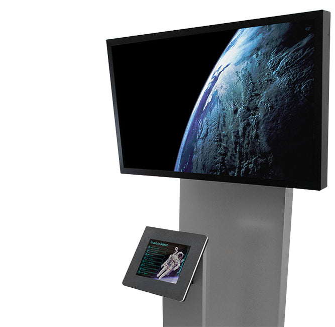 A standing kiosk enclosing both an iPad and a separate monitor. The iPad displays a selection menu while a video plays on the separate display.