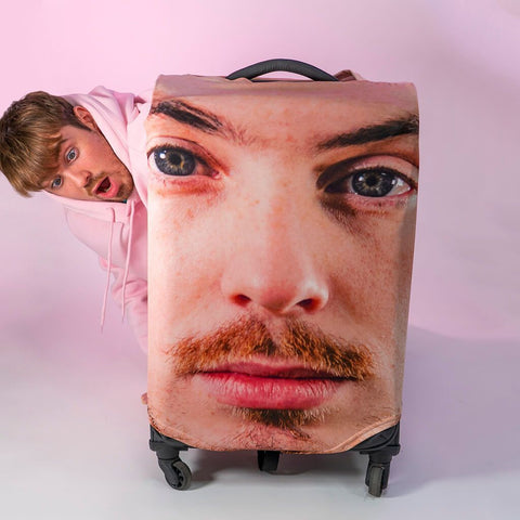 man peeking behind a suitcase with pesonalised case skin with his serious face printed on it