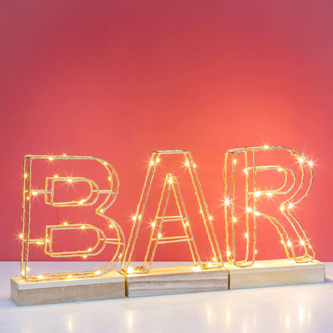 Light Up Wire Frame - A to Z spelled BAR in front of a pink wall background on a white table