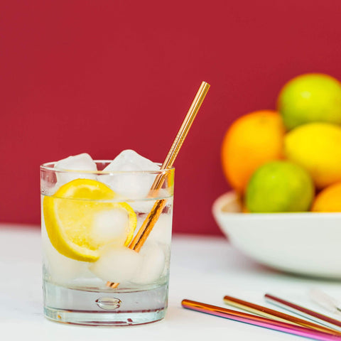 gold metal straw in an drink with lemon slice with other colourful metal straws on a white table