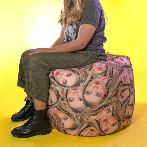 woman sitting on personalised bean bag with many faces printed on it