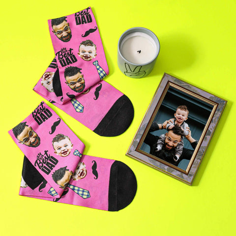 personalised pink best dad socks with father face beside a photo of dad and baby son on a yellow table with a cup of coffee