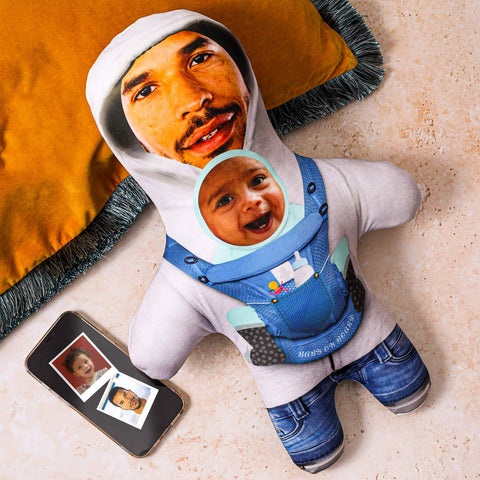 mobile cell phone with a photo of dad and baby son beside a doll mini me personalised wearing a blue jumper with father and son face