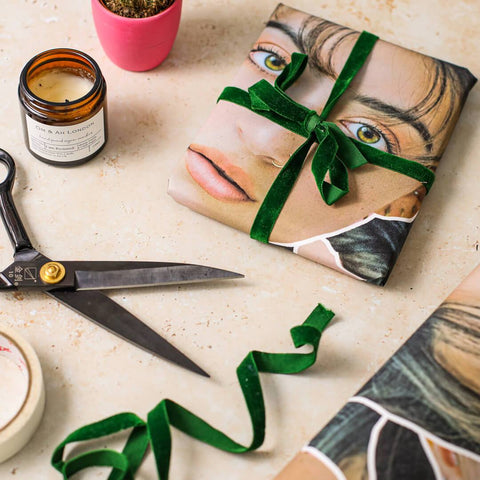 scissors tape green ribbon and personalised face wrapping paper with woman's face on top of the table