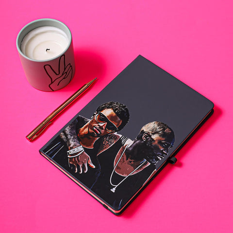 personalised notebook journal of father son hand drawn faces on a black background on pink table with a pen and a cup of coffee