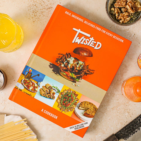 orange Twisted: A Cookbook on kitchen table with drinks nuts and pasta